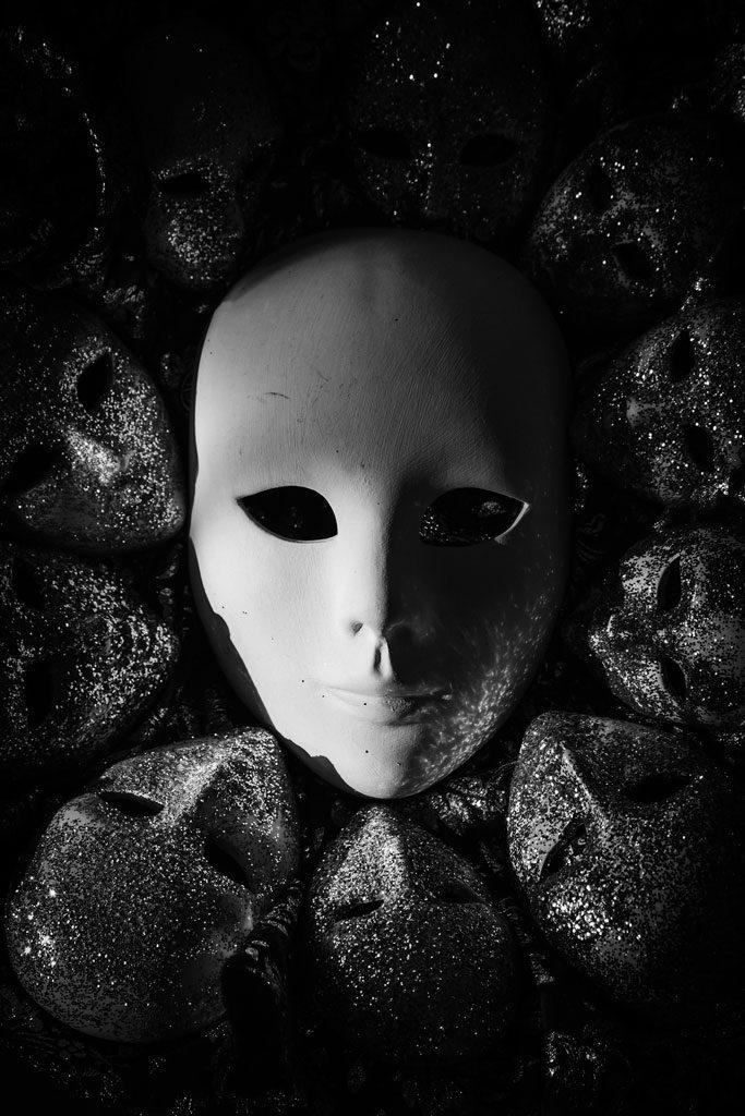 Maskenmacht: Fantasyroman. Bild: Weiße Maske inmitten von glitzernden Masken.